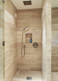 Badet er kledd med Travertin Romano på både gulv, vegger og vaskebenker. I dusjen kan man velge mellom takdusj og hånddusj fra Tapwell. En hylle i veggen gjør plass for shampo og dusjsåpe.