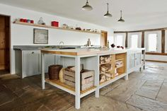 Hampshire Hop Kiln open plan kitchen with slate flooring, the Osea Island with oak lined open shelving and perforated zinc doors and custom made handcrafted cabinets. Long House. Slatted shelving. Georgian.