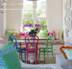 Bold graphic fabrics mixed with different colored bentwood chairs = cozy breakfast nook