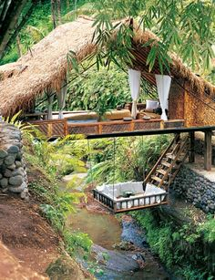 """The unusual Bridge House straddles the river, and a """"giant baby cradle"""" is suspended from it. According to Garland, this retreat is difficult to leave. """"It's like adult kindergarten. Deep in the gully, the river is gentle and quiet, and the air is always cool and breezy."""