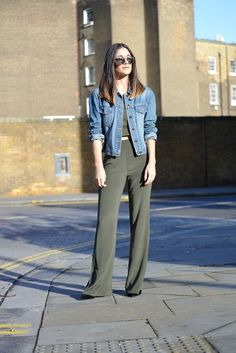 Anisa Sojka styles khaki green Keepsake high-waisted wide-leg silk trousers and crop top bodice from Fashion Bunker | White oversized Oui coat | Blue short denim jacket | Brown tortoiseshell Taylor Morris Eyewear Rollright Havana sunglasses with silver tinted mirrored lenses | Fashion blogger street style shot in London in front of a brick wall by David Nyanzi