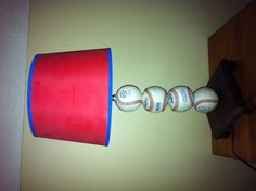 Baseball lamp made from foul balls. Drill a half inch hole in the baseballs and a wooden base. Thread a half inch hollow metal rod through the baseballs and base. Use a make-a-lamp kit to make it light up. Glue small wooden cubes under the base to get it off the ground and make room for the chord. Choose or decorate a shade of your choice.