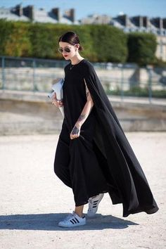 Street Style: All black flowing maxi dress + cape ensemble worn with black and white Adidas sneakers.