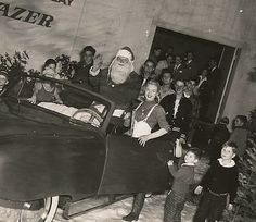 """Marilyn Monroe & """"Santa Claus"""" participating in a publicity event to promote the new Darrin/Kaiser-Frazer car, 1946."""