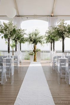 Gorgeous wedding ceremony decor with tall white and green flowering branch arrrangements.