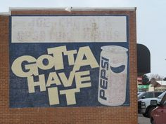 A Pepsi sign on the side of a building downtown
