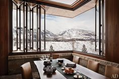 The dining room, featuring a retractableTischler und Sohn window that looks out to Aspen Mountain, is anchored by a BDDW walnut-slab table.