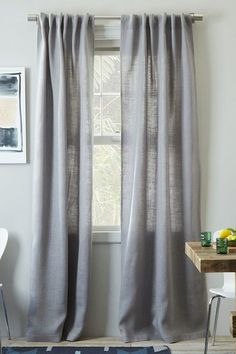 Curtains don't just keep prying eyes out, they frame your room. Try a soft, almost-opaque grey for summer. And, if you're looking to make your ceilings seem taller, try raising the curtains higher than the windows.