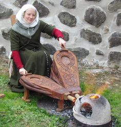 14th century woman working double bellows to heat a little casting furnace.