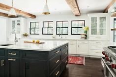 Stunning black and white kitchen is accented with rustic wood ceiling beams and Goodman Hanging Lamps hung over a black oak island complemented with brass pulls and a white quartzite countertop finished with an undermount sink and polished nickel gooseneck faucet.
