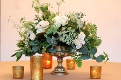 Other tables will have a cylinder vase filled with magnolia, dusty miller, olive, and silver dollar eucalyptus foliages with queen anne's lace, white ranunculus, ivory garden roses and fresh lavender