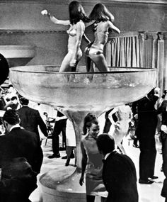 Roseann Williams and Tara Glynn dance in a giant champagne glass in P.J. (1968)