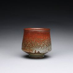 This stoneware cup has a combination of iron red and wood ash glazes. Together they create the flowing pattern and color variations. The inside