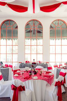 Los Angeles wedding at the Delancey Street Foundation reception hall set up with tables red tablecloth and napkins with white chairs and red ribbon decor with black and white stripped table runners