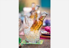 Na mesa posta, cada convidado tem seu recipiente com gelo para manter a cerveja ou o refrigerante no ponto. Bebida quente, nunca mais!