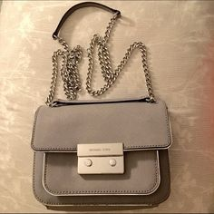 ⚡ONE HOUR ️SALE⚡️Michael Kors Carine Bag Authentic Michael Kors bag. Used this only a few times! This bag had a gray exterior with shiny silver lining. The middle has the silver clasp to unlock. The strap is a silver metal which you can do a cross body wear and pull together for a shoulder bag wear. Lots of compartment space and card slots. Still in great condition: Minor scratches on the lock and a tiny glue stain shown in the third picture.  ❣OFFERS ARE WELCOME  ❣I SHIP THE VERY NEXT DAY…