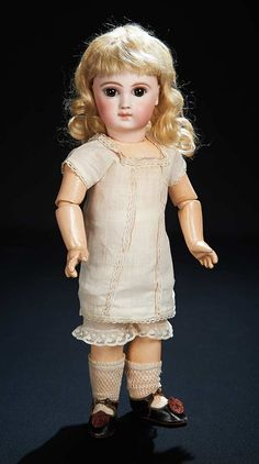Marks: 4 (head) Jumeau Medaille d'Or Paris (body). Comments: Emile Jumeau,circa 1878. Value Points: very beautiful bebe with rich eye decoration,finest quality of bisque,soft mohair wig,original body and body finish,original chemise,socks,and shoes impressed with full figure of doll by Alart.