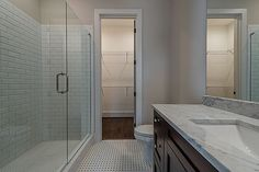 """This modern style bathroom features an espresso cabinet with carrara marble countertop, black and white basket weave tile floor and beveled 3""""x6"""" subway tile."""