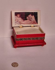 The Olympia Chest, a miniature red orange romantic wooden inlay chest, replica Manet nude painting. 1 to 12 dollhouse scale. Made in USA.