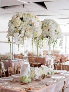Tall centerpieces with orchids, roses and candles for wedding reception