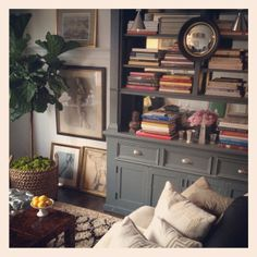 built-in bookshelves, gallery wall with propped art, fiddle-leaf fig, Moroccan rug, dark wood furniture, convex miror