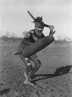 A Luritja man demonstrating method of attack with boomerang under cover of shield (1920).