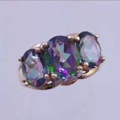 10k yellow gold ring set with 3 oval mystic topaz color change gemstones and 4 teeny diamond accents; 2 on each side. Mystic topaz gems are