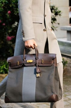 This weekender by Hermes will make you want to plan a trip! Dark gray with a lighter gray stripe & brown leather accents, this overnight bag is the perfect accessory.