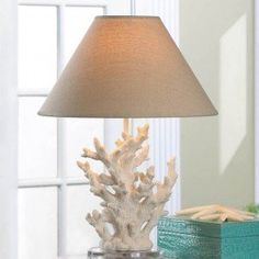 This stunning table lamp features artistically rendered ivory sprigs of coral topped with a handsome neutral-color shade. Turn on the lamp and your room will light up with a warm and inviting glow. A splash of seaworthy style to light up your life!  Item weight: 4.2 lbs. 13 3/4″ x 13 3/4″ x 18 5/8″ high; base: 5 7/8″ x 8″ x 14 1/4″ high; shade: 13 3/4″ diameter x 7 5/8″ high. Polyresin, glass, and fabric shade. Type A, maximum Watt 40 light bulb not included.