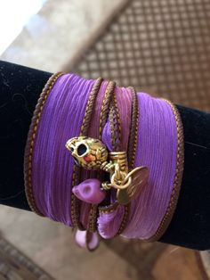 This is a purple tie dyed silk ribbon wrap bracelet or anklet. The edges are hand sewn. I added the gold bail. I put on the skull and roses charm