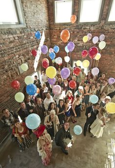 Wedding group photo with guests holding balloons