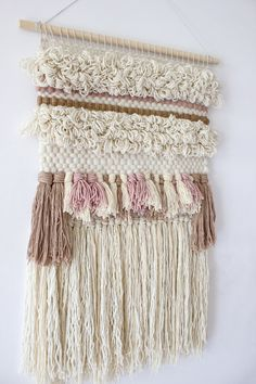 """This woven wall hanging is a true eye catcher and will be perfect addition to your gallery wall, living room or nursery. This neutral weaving piece with touches of pink, nude/beige is made from merino roving, merino wool, wool and cotton. Colours are true but please be aware that there may be differences between my monitor and yours.  Hung on a 51 cm (20"""") wooden dowel, this weaving hangs 81 cm (32"""") long from the dowel to end of fringe, and is 47 cm (18,5"""") wide (widest point).  This it..."""