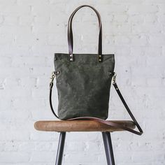 This beautiful tote is handmade using quality Martexin Waxed Canvas (olive green canvas pictured). Waxed canvas wears similar to leather over time. It is strong, durable, water-resistant, rugged but beautiful. It also softens a bit with use. This tote features genuine leather shoulder straps and a detachable genuine leather cross body strap. Straps are securely fastened with metal rivets and leather washers. Also includes a magnetic snap closure, and one interior slip pocket. Standard lining…