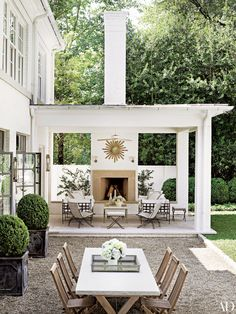 Sofas by Janus et Cie and 1950s French woven chairs from the Nicholson Gallery beckon from the terrace of designer Suzanne Kasler's Atlanta home; the sunburst mirror is vintage.