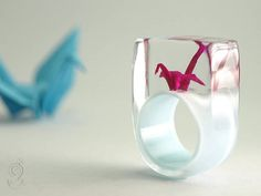 ORIGAMI CRANE A marvelous, handmade unique for an long, happy life and wisdom – they say. So to say, that the gods fulfill a wish, if you folded 1000 cranes. Well then only 999 are missing... On a light blue ring stands a mini-crane folded by hand made of pink paper. The ring is very light and despite of the size extremely good to wear. Moreover it is a hand charmer and always an eye-catcher. And who knows, maybe he brings really luck :-)  SIZE/DIMENSIONS/WEIGHT Ring size: 53,4mm / US: 6 1/2…