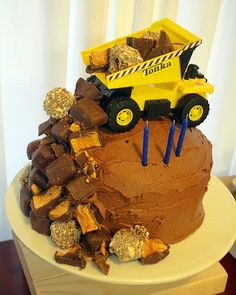 Construction themed party -Love this cake becuase it reminds me of a friend that said she didn't decorate cakes but she stuck things in icing really well. Probably cost the same as a storebought cake but you end up with a truck to play with