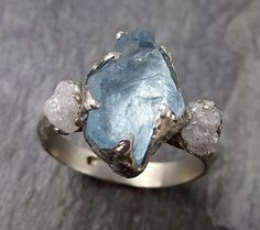 Raw rough aquamarine surrounded by raw conflict free diamonds. I hand carved this ring in wax and cast it in solid 14k white gold using the lost wax casting process. This one of a kind raw gemstone ring is a size 7 it can be sized. The aquamarine stone measures about 12mm X 8mm. The rough