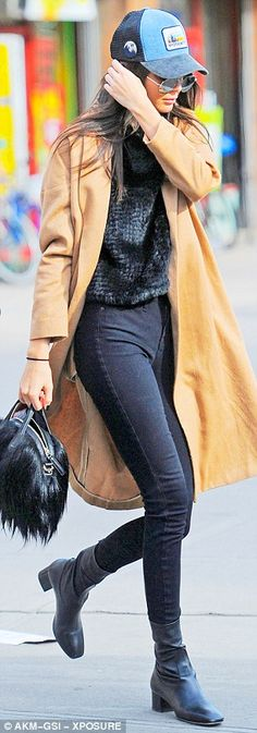 Going undercover: The young celebrity tried to stay low key in a a black jersey and leggings under a camel-coloured overcoat with black bootees and a black and blue cap that she jammed over her brunette hair