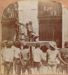 A Filipino being executed by garrote, a strangulation machine, in 1898. The garrote consisted of a brass collar with a back piece pushed forward by the impulse of a big screw working through a post. When the executioner turned the handle of the screw, the back piece in the collar pressed against the top of the condemned's spine, thereby snapping the spinal cord.