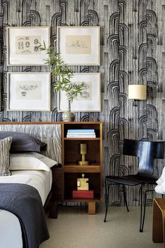 Inside a Palm Springs home, the guest room's eye-catching wallpaper is a Kelly Wearstler design, punctuated by Frank Gehry drawings and a sleek black chair by Donghia.