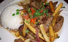 Lomo Saltado (strips of sirloin marinated in vinegar, soy sauce and spices, then stir fried with red onions, parsley and tomatoes. It is traditionally served over white rice with homemade French fries that look more like potato wedges) Peruvian Dishes, Peruvian Cuisine, Peruvian Recipes, Lomo Saltado, Asian Recipes, Mexican Food Recipes, Asian Foods, Beef Steak Recipes, Homemade French Fries
