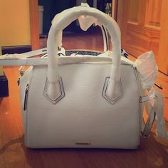 "Rebecca Minkoff White Perry Satchel Brand new, never used, White Rebecca Minkoff Perry Satchel in white is the ideal everyday carryall. The silhouette is ultra-feminine, and the side zippers and gold hardware add a touch of glam. 15.75""W x 11""H x 7""D, Genuine leather, 13.5"" adjustable detachable shoulder strap drop, 4"" handle drop, Dual top zipper closure, Two exterior expandable zipper slip pockets, One interior zipper pocket, Three interior slip pocket, Custom lining. Dust bag included…"