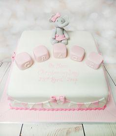 Lovely white and pink christening cake, with a very cute elephant model. #christeningcake #whiteandpinkcake #elephantmodelcake https://www.craftycakes.com/