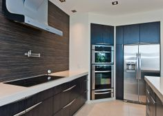 Alair Homes | Nanaimo | Custom Homes - The sleek open kitchen design allows for a clean, contemporary space, while stainless steel appliances in conjunction with the zebra-wood backsplash enhance the modern, urban feel.