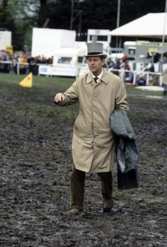 Prince Philip, Duke of Edinburgh, wearing a mac and top hat, trudges through the mud during a wet Derby Day on June 1990 in Epsom, England. Elizabeth Philip, Princess Elizabeth, Queen Elizabeth Ii, Prince Phillip, Prince Charles, Royal Navy Uniform, British Monarchy History, Photos Of Prince, Elisabeth Ii