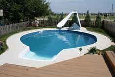 Sensational Inground Pool Kits With White Slide Decor And Tile Edging Combined With Wooden Deck Flooring