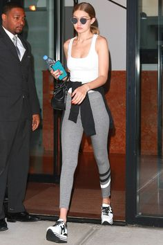 In a white tank top, grey striped leggings, platform sneakers, a black leather handbag, reflective sunnies and a black sweatshirt wrapped at the waist.