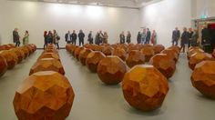 """Ai Weiwei, """"81 Wooden Balls"""". 2012. Installation of wooden polyhedrons, each of them constructed using the joining methods of traditional Chinese furniture without use of paste or staples. The shapes are based on Da Vinci´s polyhedral sketches, and they are modeled after a plastic toy belonging to his son. Ai Weiwei led his workshop through two years of experimentation before finally completing this complex, minimalistic installation using lost crafting techniques."""