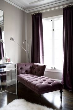 Plum panels match the tufted velvet on the chaise and give this simple room a luxurious look. To keep things from looking heavy and drab, the velvet is paired with light walls and shiny accents: metal floor lamp, leaning mirror, Lucite table.