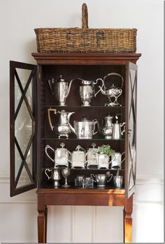 """RENOVATION STYLE:   This cabinet in the dining room once had no legs – the homeowner had her carpenter add them!!  Inside is a collection of antique and hotel silver."""